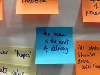 Sticky note saying 'The team is the unit of delivery'