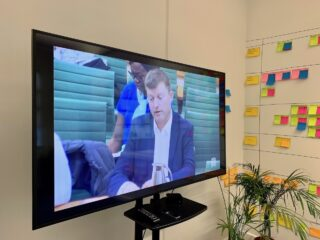 A photo of a TV screen in the PD office, showing Tom Loosemore giving evidence to the House of Commons Science and Technology Select Committee on 27 Nov 2018